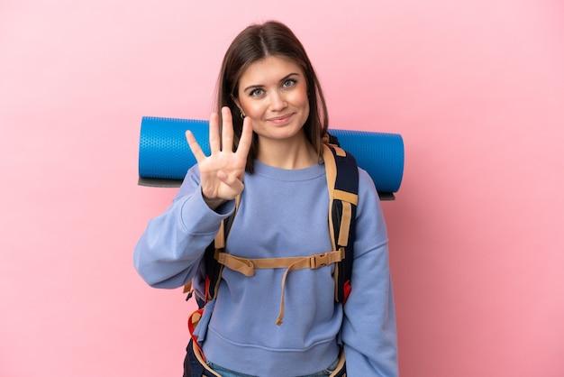 Donna giovane alpinista con un grande zaino isolato su sfondo rosa felice e contando quattro con le dita