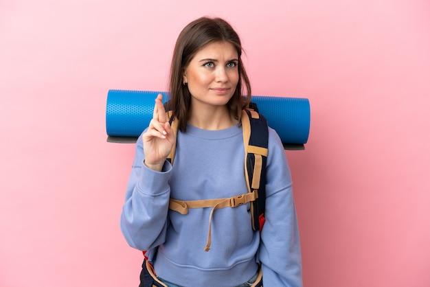 Giovane donna alpinista con un grande zaino isolato su sfondo rosa con le dita incrociate e augurando il meglio