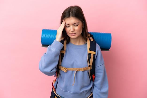 Giovane donna alpinista con un grande zaino isolato su sfondo rosa con mal di testa
