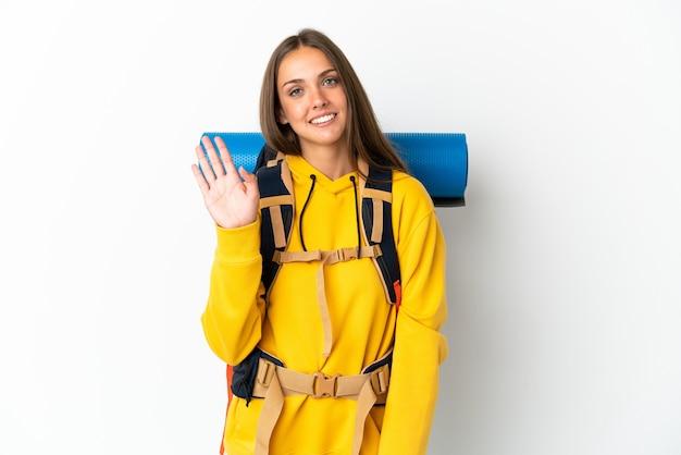 Giovane donna alpinista con un grande zaino su sfondo bianco isolato che saluta con la mano con l'espressione felice