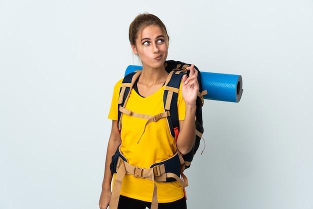 Giovane donna alpinista con un grande zaino isolato su sfondo bianco con le dita che si incrociano e che desiderano il meglio