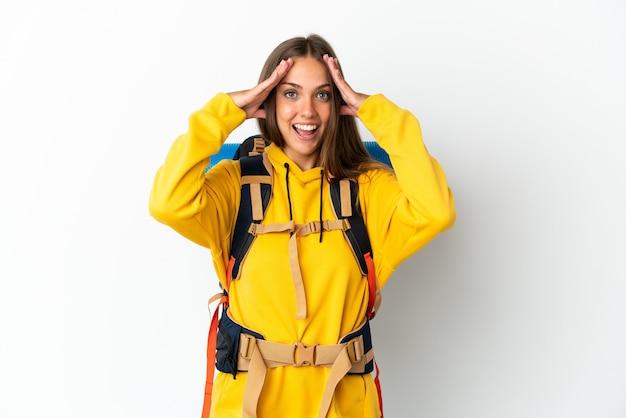 Giovane donna dell'alpinista con un grande zaino sopra fondo bianco isolato con l'espressione di sorpresa