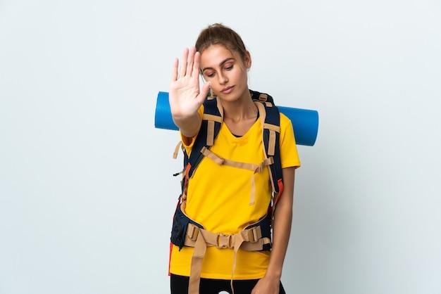 Giovane donna alpinista con un grande zaino isolato sul muro bianco che fa gesto di arresto e deluso