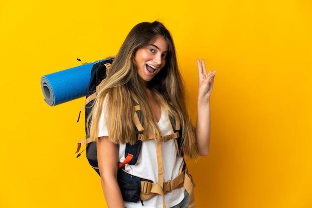Giovane donna alpinista con un grande zaino isolato su sfondo giallo sorridendo e mostrando il segno di vittoria