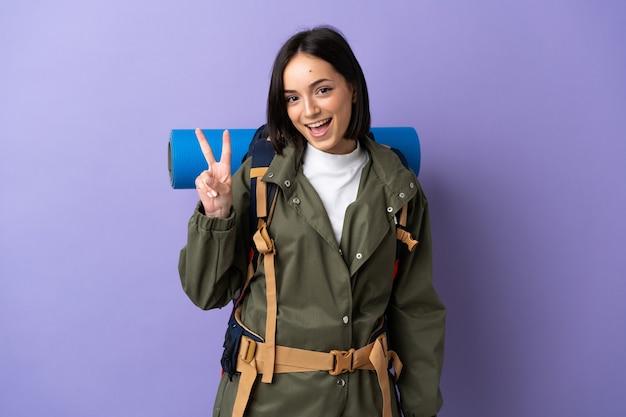 Donna giovane alpinista con un grande zaino che sorride e che mostra il segno di vittoria
