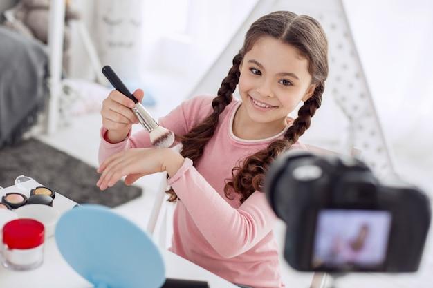 Giovane mua. affascinante ragazza pre-adolescente minuta prova una nuova cipria applicandola sulla mano durante le riprese di un video tutorial di bellezza