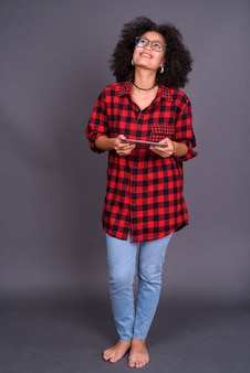 Giovane multietnica donna afro-americana hipster con capelli afro contro il muro grigio