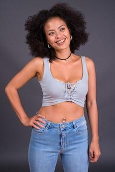 Giovane donna afro-americana multietnica con i capelli afro contro il muro grigio