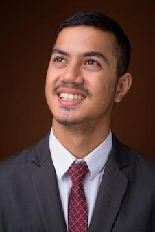 Giovane uomo d'affari asiatico multietnico contro il muro marrone