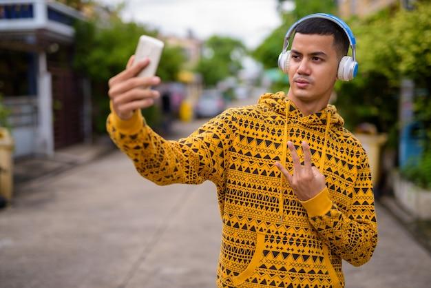 Giovane uomo asiatico multietnico nelle strade all'aperto
