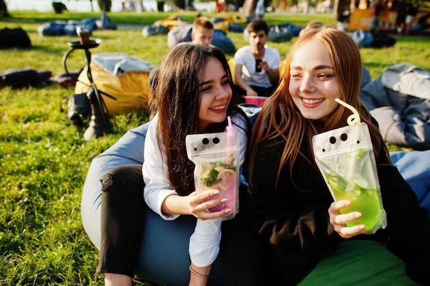 Giovane multi etnico gruppo di persone che guardano film al puff nel cinema all'aperto. due ragazze con cocktail mojito.