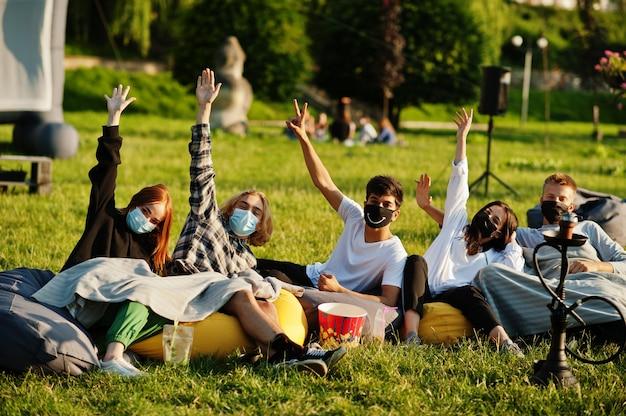 Giovane gruppo multietnico di persone che guardano film al puff nel cinema all'aperto indossano una maschera durante la quarantena del coronavirus covid.