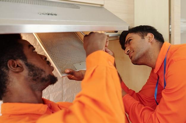 Giovani tuttofare multietnici in arancione indossano la rimozione del filtro antigrasso mentre riparano insieme la cappa da cucina
