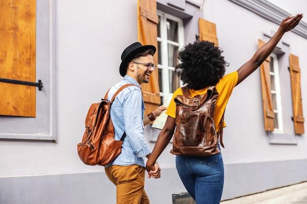 Giovane coppia multiculturale mano nella mano e visitare la città. uomo che tiene una mappa.
