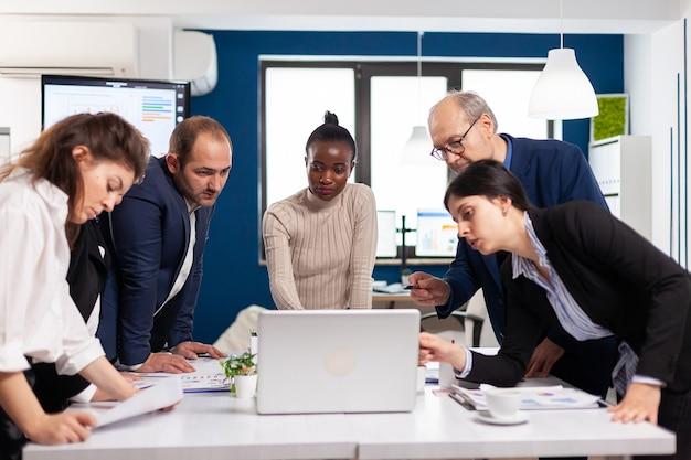 Gruppo di giovani lavoratori multiculturali che parla guardando il laptop e analizzando i dati digitali