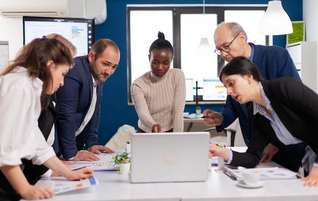 Gruppo di giovani lavoratori multiculturali che parlano, guardano il laptop e analizzano i dati digitali colleghi multietnici che lavorano pianificando una strategia finanziaria di successo che discutono in ufficio