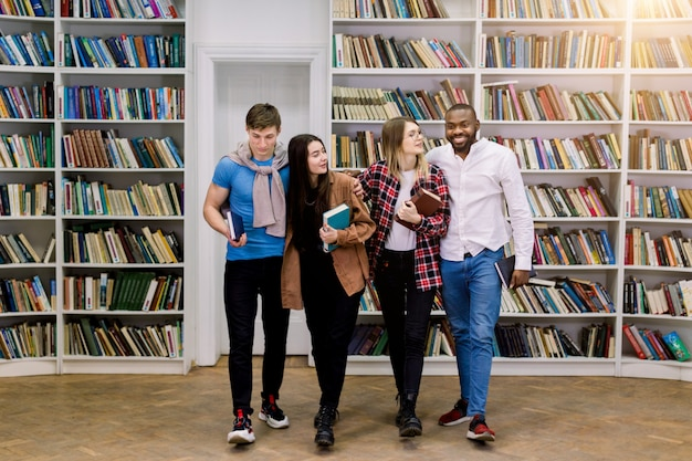 Giovani studenti multietnici, ragazze e ragazzi in possesso di libri, abbracciati, in piedi in biblioteca sullo spazio degli scaffali dei libri