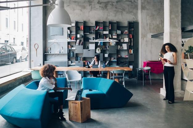 Giovane freelance multirazziale che lavora in ufficio di co-working e che interagisce con il dispositivo digitale