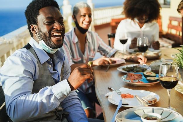 Giovani multirazziali che mangiano e bevono vino rosso mentre indossano maschere protettive - concetto di distanza sociale - focus sul volto dell'uomo africano