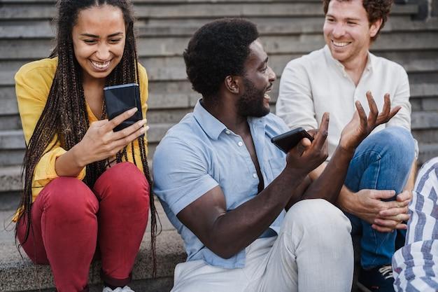 Giovani multirazziali che usano i telefoni cellulari all'aperto in città - focus sulla faccia della ragazza africana