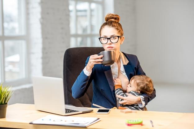 Giovane imprenditrice multitasking che allatta il figlioletto con il seno mentre fa una pausa bevendo caffè in ufficio