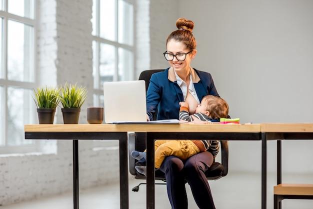 Giovane imprenditrice multitasking che allatta il figlioletto con il seno mentre lavora in ufficio