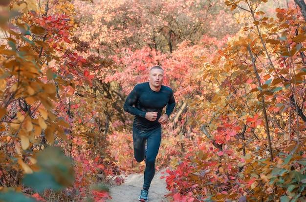 Un giovane atleta muscoloso in leggins e maglietta sportivi neri attraversa un bellissimo bosco autunnale rosso.