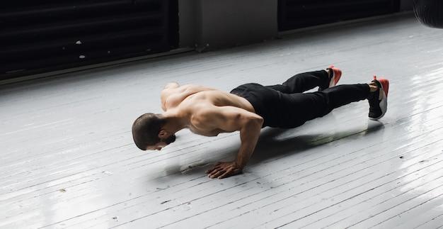 Giovane atleta muscolare facendo flessioni sulle sospensioni. foto di alta qualità