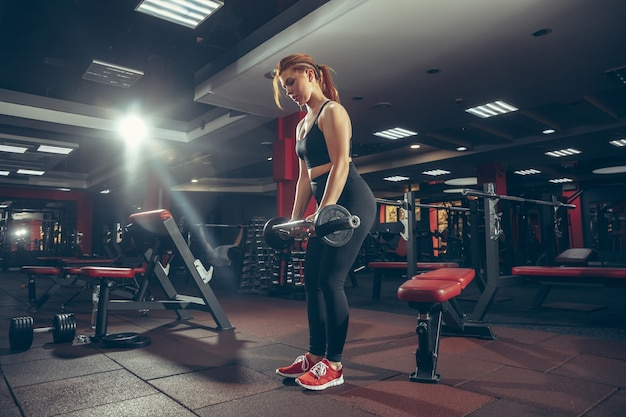 Giovane donna caucasica muscolare che si esercita in palestra con uno stile di vita sano di benessere dell'attrezzatura