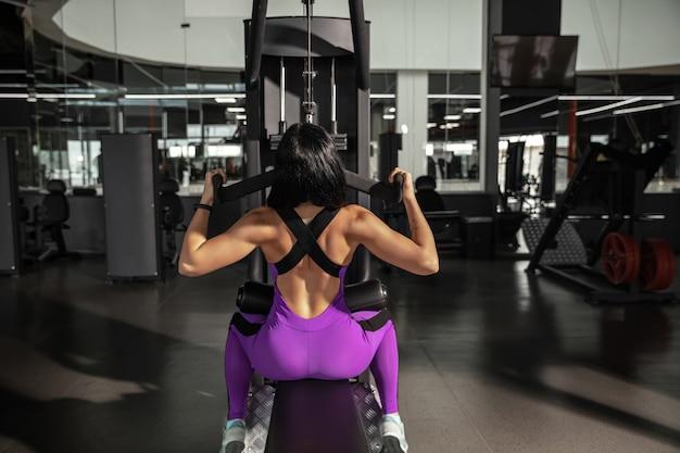 Giovane donna caucasica muscolare che si esercita in palestra con attrezzature