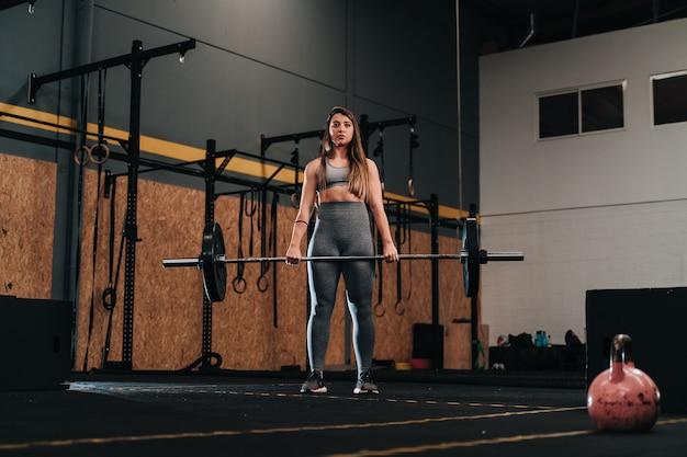 Giovane ragazza muscolare che solleva un bilanciere di peso morto in una palestra crossfit