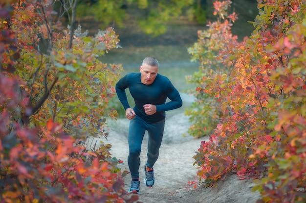 Un giovane jogger muscoloso in leggins neri e camicia corre nella colorata collina della foresta autunnale rossa.
