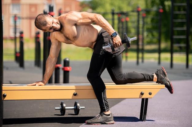 Giovane uomo muscoloso in leggins neri che si appoggia sul banco durante il sollevamento di manubri pesanti sul campo sportivo