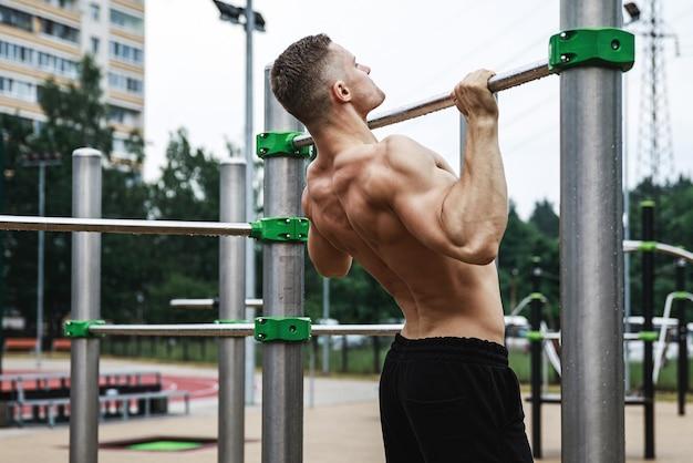 Uomo giovane e muscoloso facendo pull-up sulla barra orizzontale