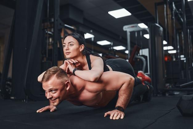 Giovane uomo muscolare facendo esercizio pushup e tenendo la ragazza formazione congiunta lezioni di gruppo teambuilding romance