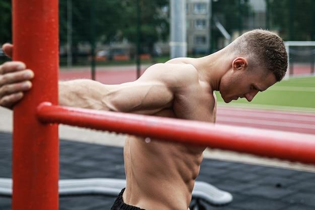 Giovane uomo muscoloso durante il suo allenamento in strada