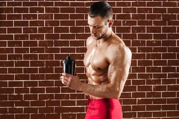 Giovane uomo muscoloso che mostra il suo corpo perfetto e shaker