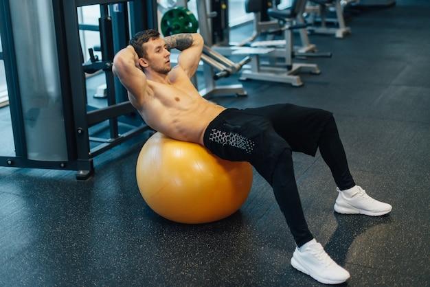 Il giovane uomo muscolare allena i muscoli addominali facendo uso della palla di esercizio