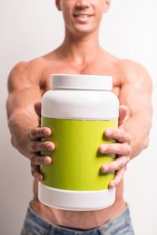 Giovane uomo muscoloso con barattolo di proteine.