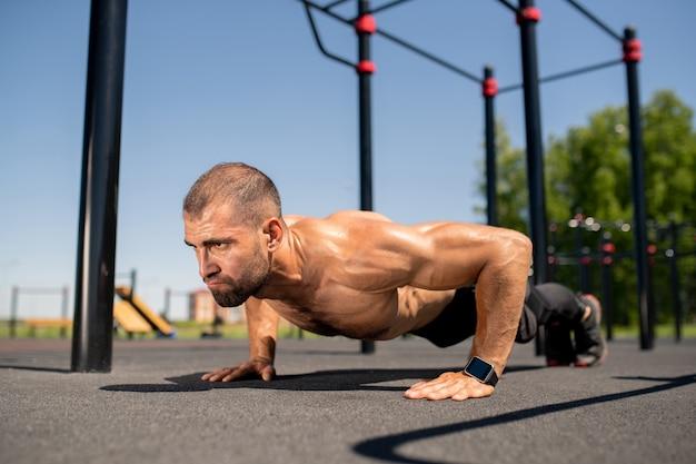 Giovane atleta senza camicia muscolare mantenendo il corpo sul campo sportivo mentre fa flessioni durante l'allenamento all'aperto