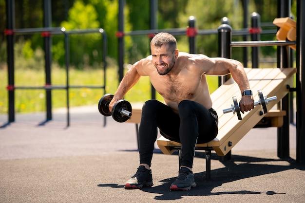 Giovane atleta senza camicia muscolare che suda mentre fa esercizio difficile per i muscoli sul campo sportivo