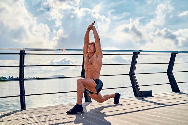 Giovane uomo muscoloso tatuato che fa esercizi di stretching la mattina presto sul molo in riva al mare