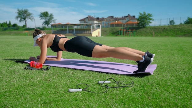 Giovane donna muscolare che indossa abbigliamento sportivo, berretto bianco e cuffie senza fili che praticano la posizione della plancia sul campo dello stadio verde con erba. ragazza che allena i muscoli addominali sulla stuoia all'aperto.