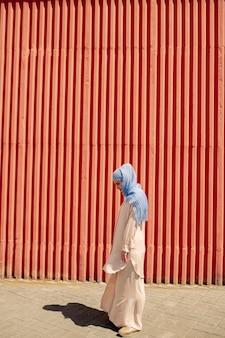 Giovane donna musulmana in abbigliamento casual e hijab in piedi in ambiente urbano sulla parete rossa