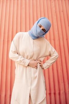 Giovane donna musulmana con la faccia nascosta dietro l'hijab blu in piedi e ti guarda