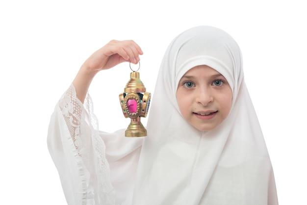 Giovane ragazzina musulmana in hijab che tiene la lanterna del ramadan