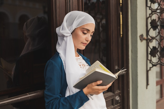 La giovane ragazza musulmana indossa l'hijab con il concetto di studente islamico e conoscenza del libro del diario