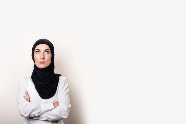La giovane donna musulmana vestita con una camicia bianca e l'hijab ha le braccia incrociate e guarda in alto