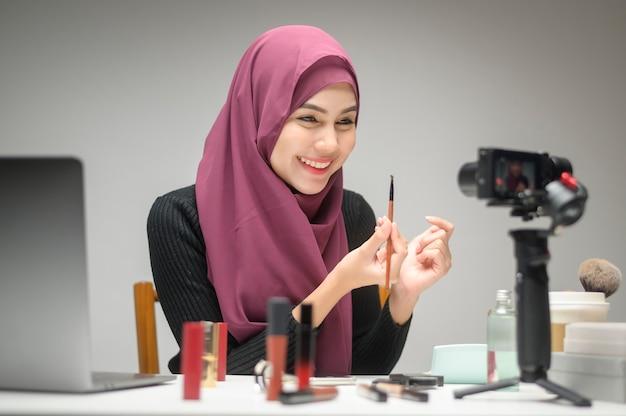 Una giovane donna musulmana imprenditrice che lavora con il computer portatile presenta prodotti cosmetici durante lo streaming live online su sfondo bianco studio, vendita online e concetto di blogger di bellezza