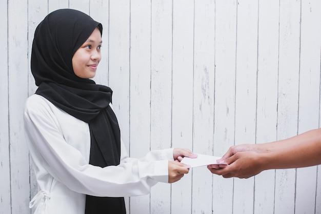 Giovane donna musulmana che dà una busta bianca per dare thr o pagare zakat fitrah come obbligo nel mese sacro del ramadan